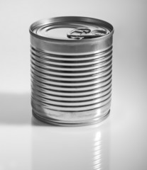 A silver tin can on a grey background.