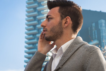 Portrait of a handsome young man talking on phone