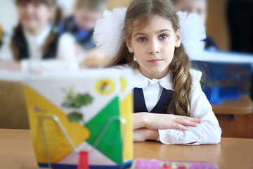 Schoolgirl sits at a school desk with notebooks
