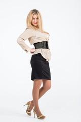 Portrait of blond girl in black skirt in the studio