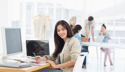 Casual woman at desk with colleagues behind in office