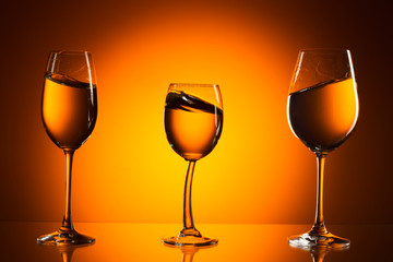 three glasses on orange background