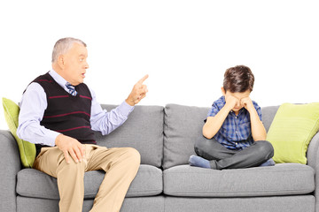 Angry grandad shouting at his nephew, seated on a sofa