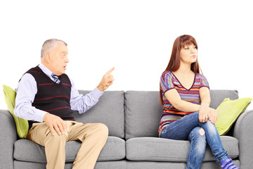 Father reprimending his uninterested daughter seated on a sofa