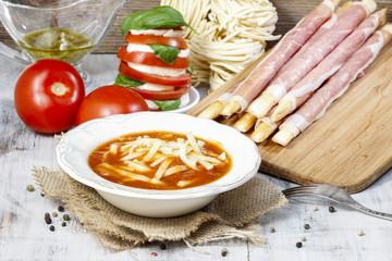 Italian cuisine: tomato soup, breadsticks with ham, caprese sala