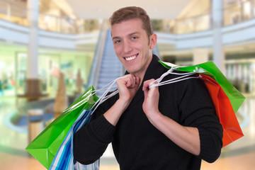 Junger Mann beim Shoppen oder Einkaufen im Geschäft