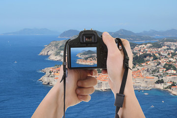 photocamera in male hands taking picture of beautiful landscape