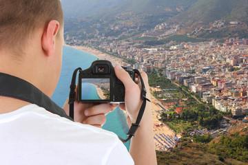 camera in male hands taking picture of beautiful landscape in Al