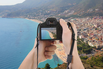 camera in male hands taking picture of beautiful landscape