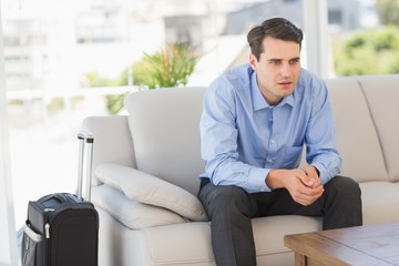 Businessman sitting on couch waiting to leave on business trip