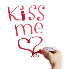 """Female hand writing """"kiss me"""" marker on a white background"""