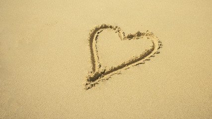 Love sign written on sand