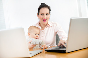 Business woman working in the office with her little baby