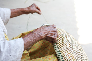 Hand of Thai Old woman weaving bamboo baskets