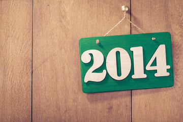 Greeting New Year date signboard front wooden background