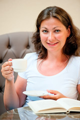 beautiful girl is drinking coffee from a white cup