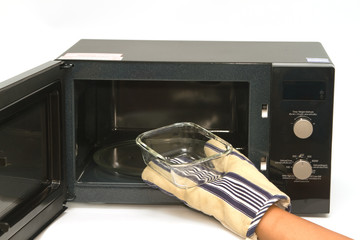 Woman heating dish in microwave
