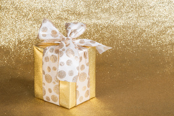 Golden gift wrapped present on gold background