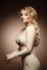 Lovely model with shiny volume curly hair. Nude makeup.