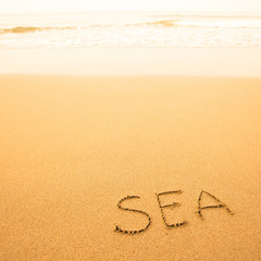 Sea, written by hand in sand on a sea beach, with a soft wave.