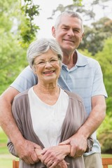 Senior man embracing woman from behind at the park