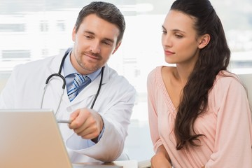 Male doctor showing something on laptop to patient