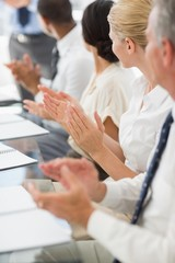 Business people clapping colleague at a meeting
