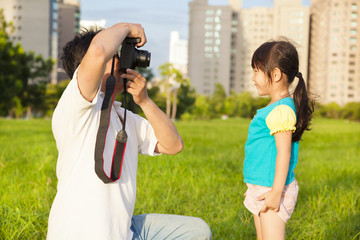 happy father taking picture with little girl in the city park