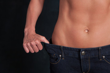 A fit attractive woman's stomach after a diet with jeans