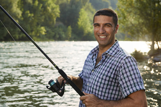 portrait of man fishing on river and holding rod