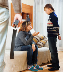 Mother and father with belt scolding teenager son