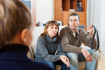 Couple with belt berating  son