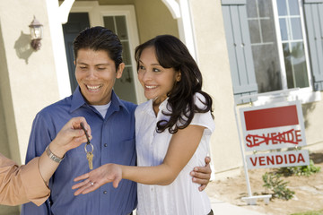 Young couple buying house taking keys