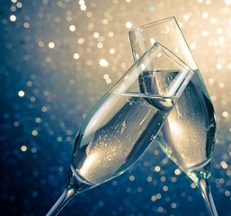 champagne flutes with bubbles on blue light bokeh background