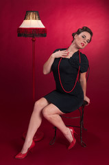 Pinup Girl in Black Dress with Posing with Lamp