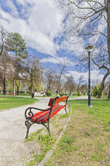red bench in spring, summer park vertical, wide angle