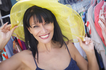 Pretty Italian Woman Trying on Yellow Hat at Market