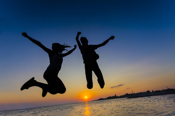 Couple jumping on sunset, colorful clear sky. Silhouette