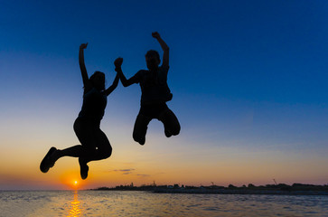 Silhouette Couple jumping on the beach at sunset