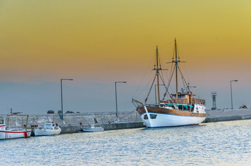 fishing boats in harbor on sunset sky
