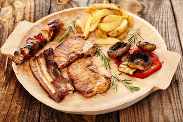 Fried pork meat with wedges potatoes  and grilled vegetables