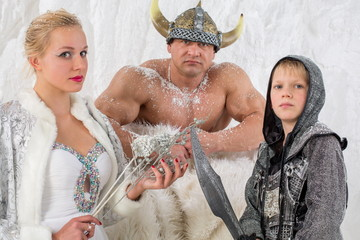 Family in historical costume viking with sword and helmet