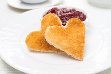 Two toast bread in the shape of heart and berry jam on the plate