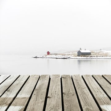 Norway Cottage on winter coast with wooden platform dock