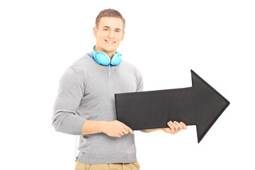 Smiling guy with headphones holding a big black arrow pointing r