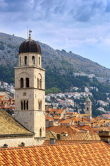Bell tower and red-orange roof on a background of mountains and