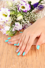 Beautiful woman hands with blue manicure near bouquet of