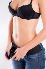 Slim woman tightening belt