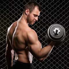 Fitness. Beautiful, strong, muscular man with a dumbbell