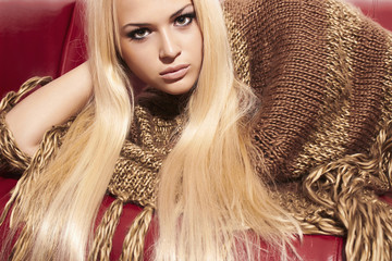 Beautiful Blond Woman on Red Leather Sofa.Beauty.Fashion.Poncho